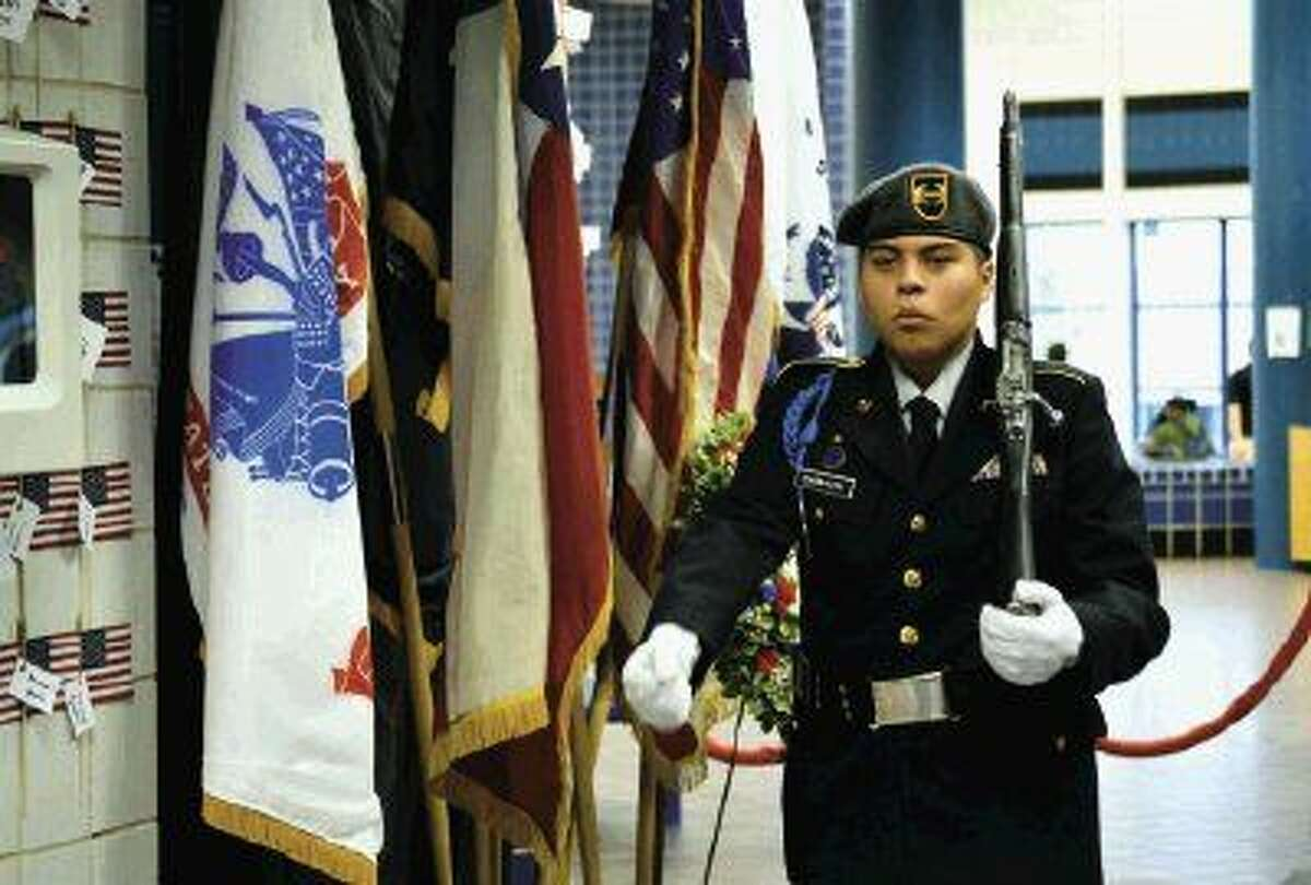 Moises Carbajal guards the wreath and flag display of the military branches at New Caney High School. The display was a recreation of the Tomb of the Unknown Soldier in Arlington National Cemetery.