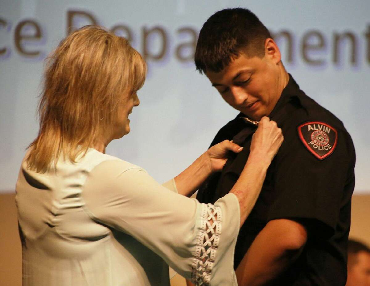 ACC Law Enforcement Academy graduate Scott Shed, of Alvin, right, receives his Alvin Police badge from his mother Jessica Shed during a graduation ceremony on May 25.