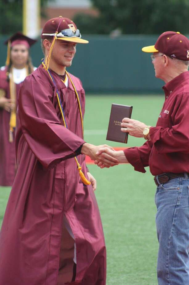 In the unlikeliest of settings, Cameron Thompson, wearing his baseball uniform under his graduation gown, receives his high school diploma from Superintendent Victor White last Friday morning at UHs Schroeder Park. He and 10 others plus a student trainer and manager, walked down the third-base line to receive their diploma. Photo: Robert Avery