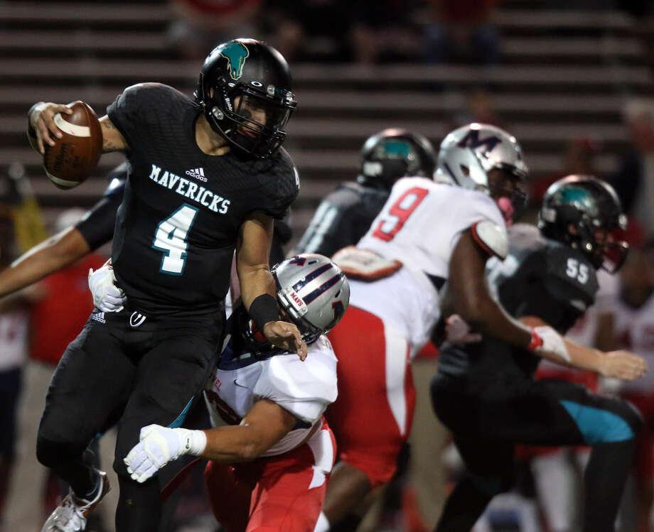 Memorial quarterback Izrael Trevino (4) tries to get away from a Manvel player Thursday night. Photo: Kar B Hlava