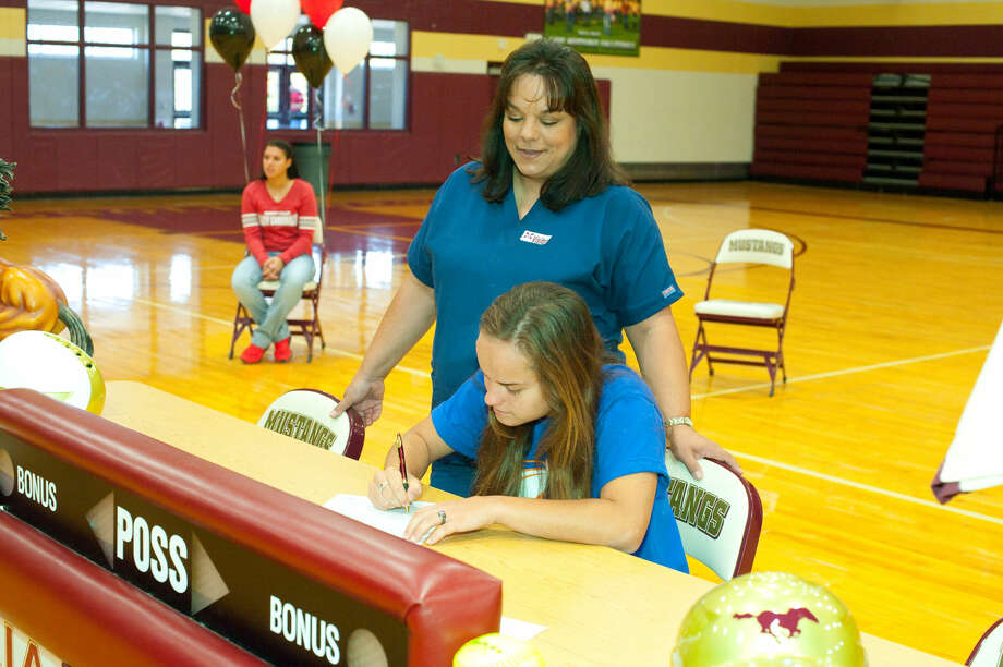 Magnolia West senior Kayci Moore signs National Letter of Intent to play softball at UT Arlington. Photo By Tony Gaines.