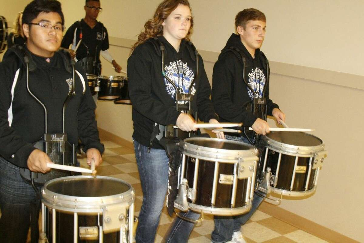 Kids piled out of classrooms as the New Caney High School marching band drum line made their way through schools in the New Caney Independent School District Nov. 12, 2014.