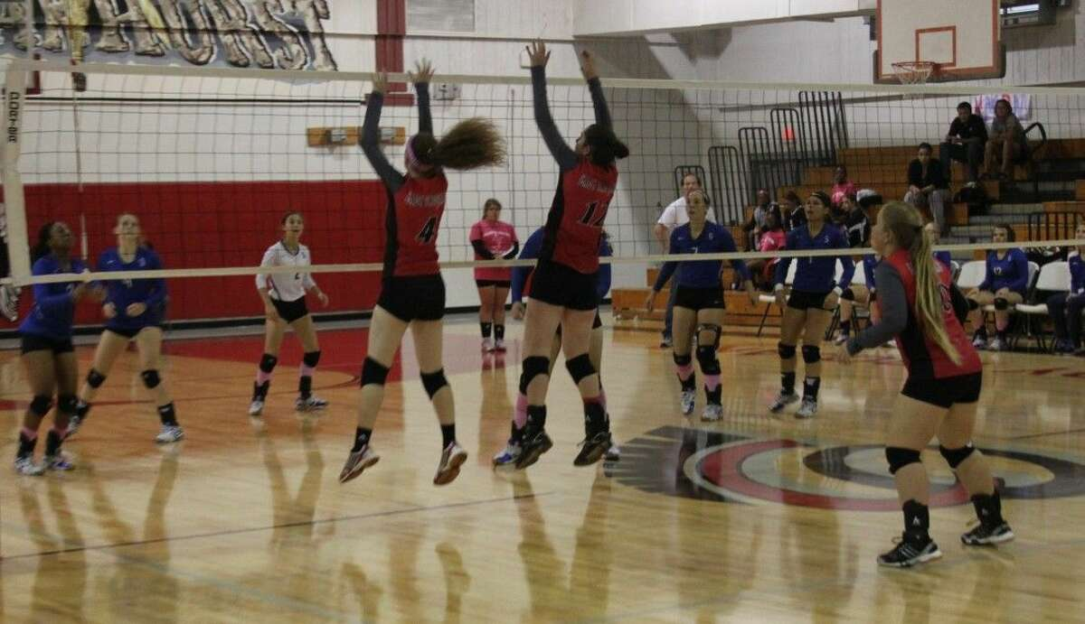 The Lady Trojans attempt to block the ball repelled by Candice Yates (3) of the Lady Pirates.