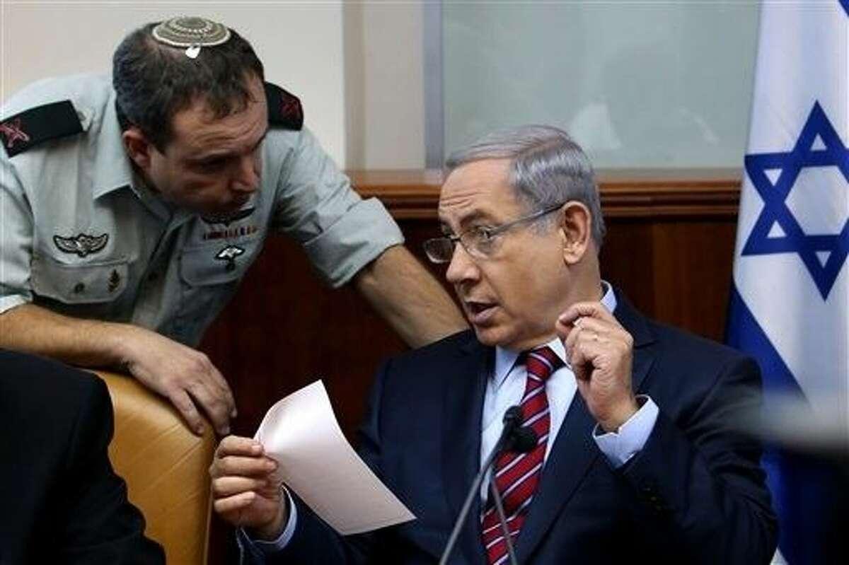 Israel's Prime Minister Benjamin Netanyahu speaks his military secretary Brigadier General Eliezer Toledano, left, during the weekly cabinet meeting at his office, in Jerusalem, Sunday.