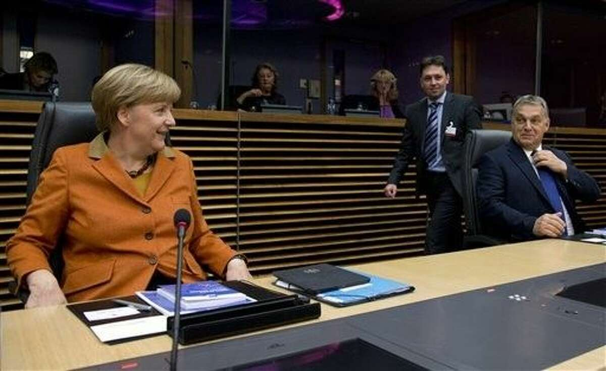 German Chancellor Angela Merkel, left, and Hungarian Prime Minister Viktor Orban, right, wait for the start of a round table meeting during an EU summit at EU headquarters in Brussels on Sunday.
