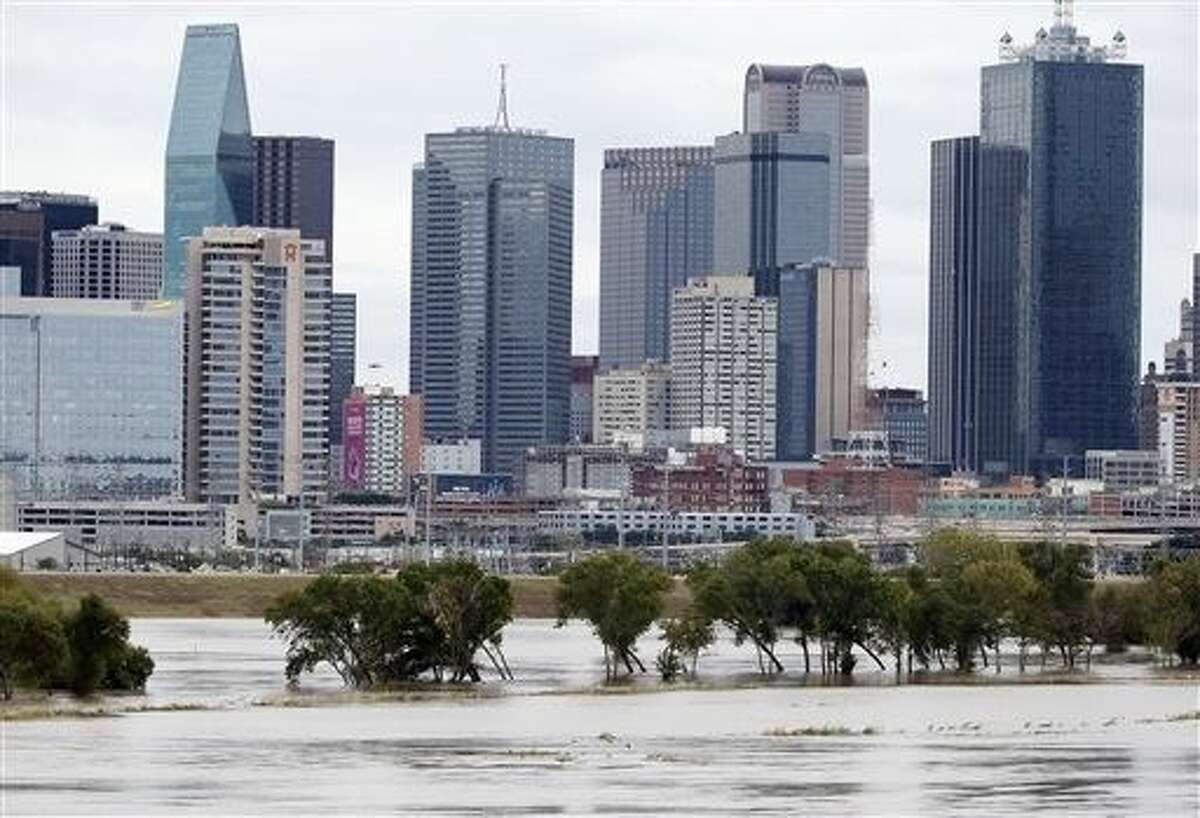 The rain-swollen Trinity River is seen with the city skyline in the background Saturday in Dallas. Southeast Texas was bracing for heavy rain late Saturday and into Sunday as the remnants of Hurricane Patricia combined with a powerful storm system that's been moving across Texas, flooding roads and causing a freight train to derail.