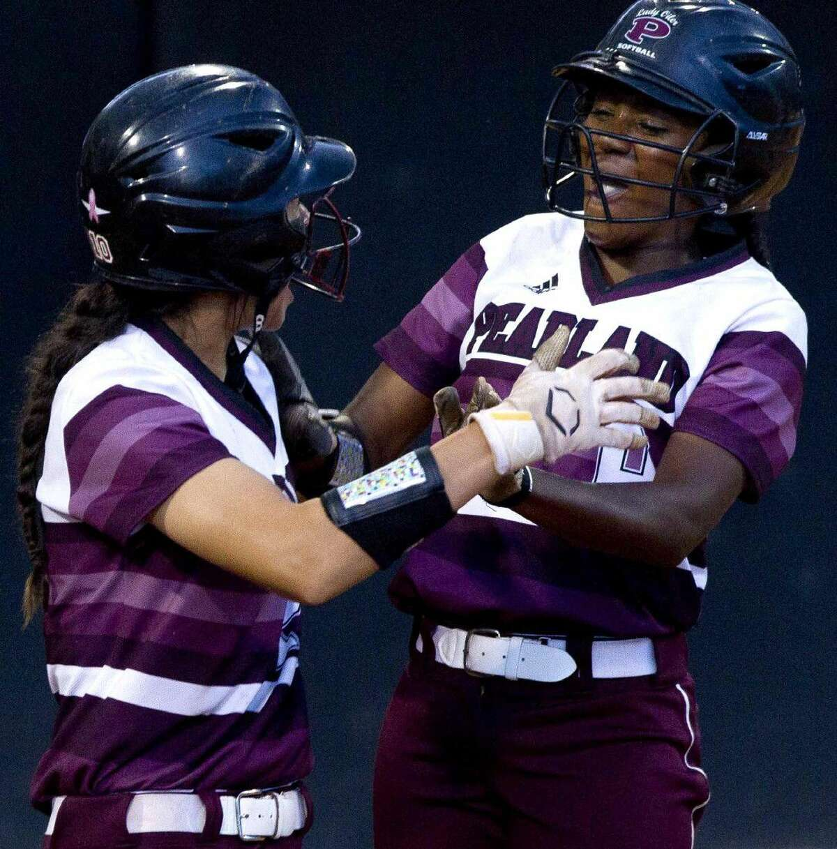 Pearland's Lindsey Stewart, right, celebrates witj Sydney Gutierrez after scoring off a two-RBI double by Lauren Shepherd during the seventh inning of a 6A semifinal game at the UIL State Softball Championships Friday in Austin. Go to HCNpics.com to view more photos from the game.
