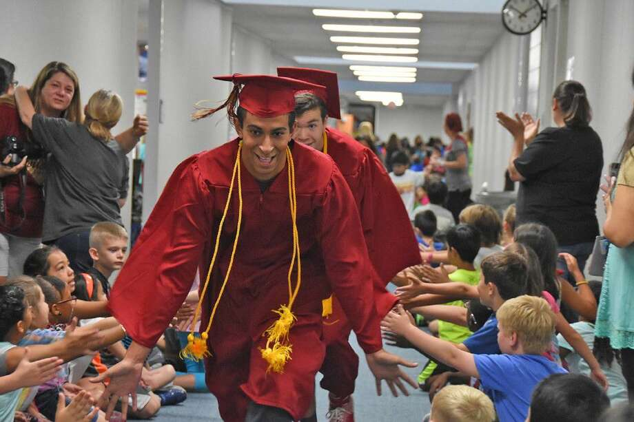 Cypress Woods High School graduating seniors Mitchell William and Matt Faga are congratulated by A. Robison Elementary School students as they parade through the hallway during a senior walk at the feeder campus on June 2.