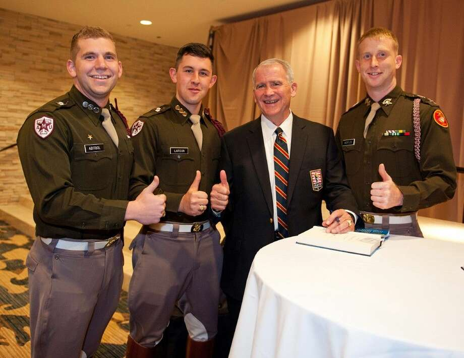 Lt. Col. Oliver North gives the Gig 'em Aggies thumbs up with, from left, Kenny Abitbol, Chris Larson and Hunter Bertles of the Texas A&M University Corps of Cadets Photo: HOLLY PAULSON