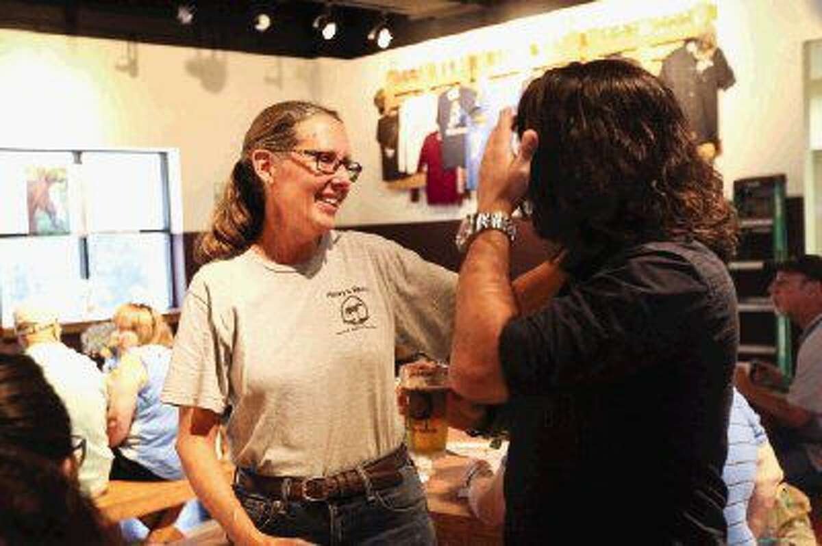 Founder Donna Stedman, left, of Henry's Home Horse and Human Sanctuary, visits with friends, family and supporters during a fundraiser on Sunday at Southern Star Brewery.