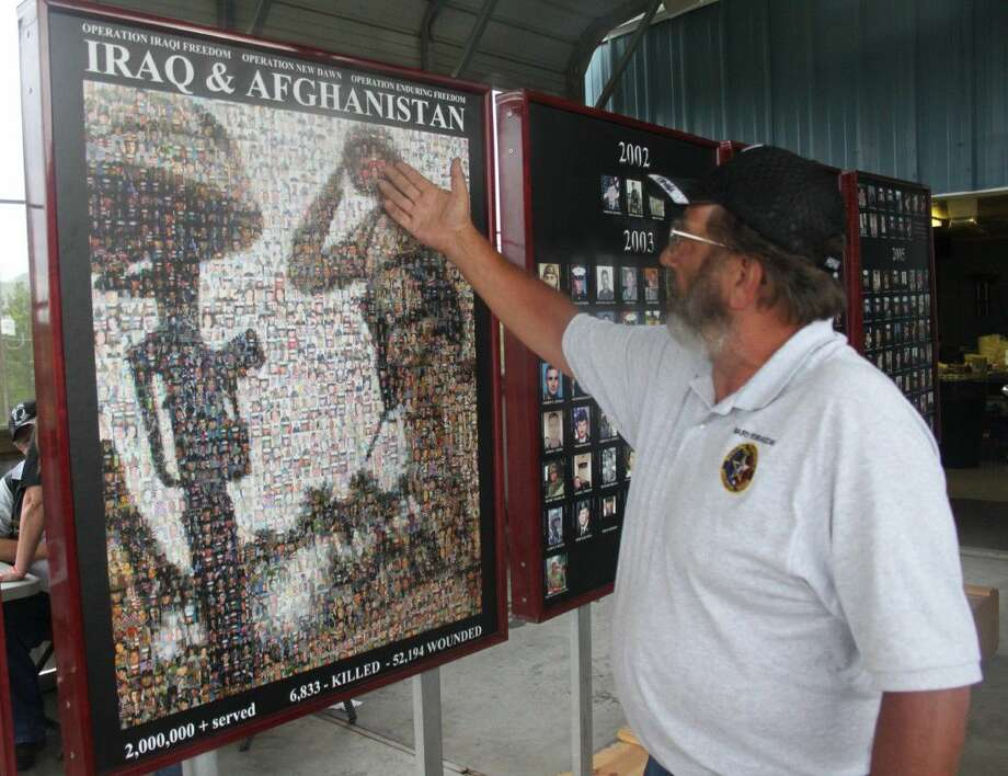 Gary Robinson displays one of a number of murals honoring fallen Texas veterans in foreign conflicts. This mural contains 1,920 images making up a larger image. The images as a whole display 640 soldiers killed in Iraq and Afghanistan, with each soldier displayed three times each. Photo: Jacob McAdams