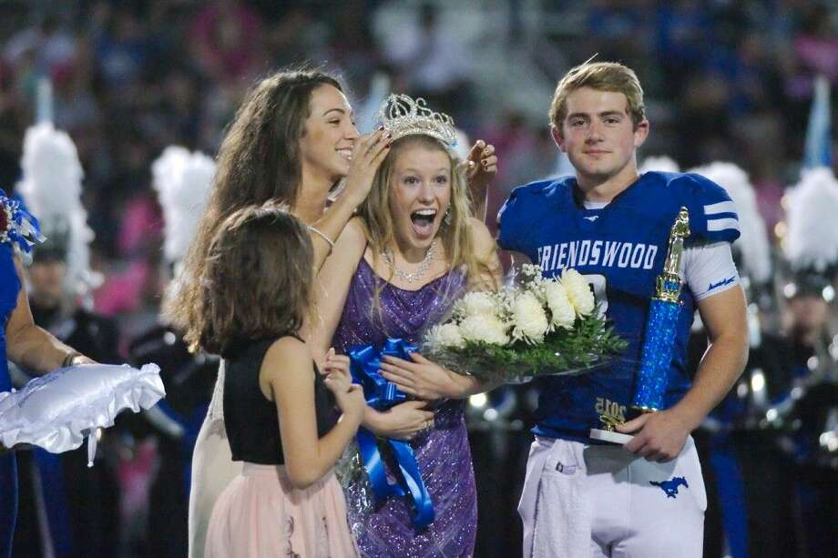 Escorted by Friendswood's Ryan Epperson (8), Skyler McHenry reacts as 2014 Homecoming Queen Maggie Roher places the crown after McHenry is named 2015 Friendswood High School Homecoming Queen during halftime of the game against Dickinson Friday, Oct. 23.
