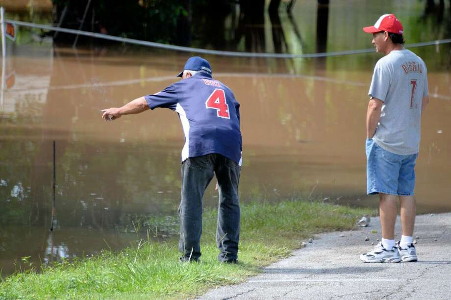 Residents, including a member of the Salinas/Linares family (right) examine flooded property along the Brazos River in Rosenberg Friday afternoon. The house was completely inaccessible due to elevated water levels from the river, and family members fear it may not be salvageable once waters recede. Photo: Craig Moseley
