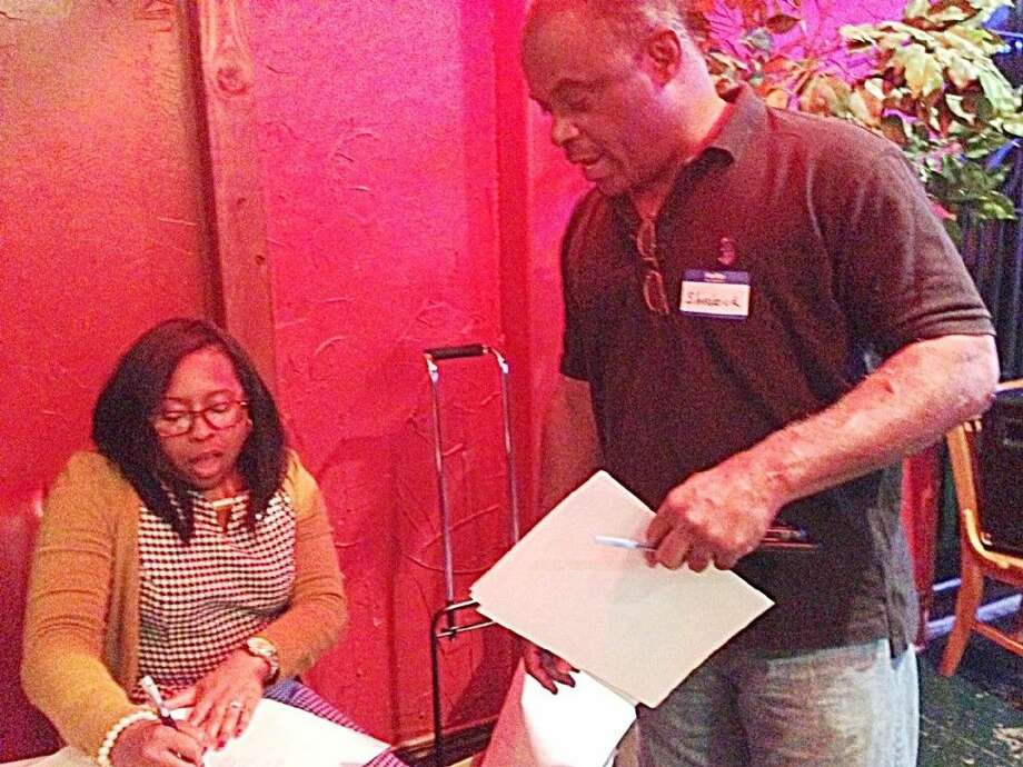 Tenesha Hudspeth helps Cypress-Tomball Democrat member Shederick Baptiste with information on early voting.