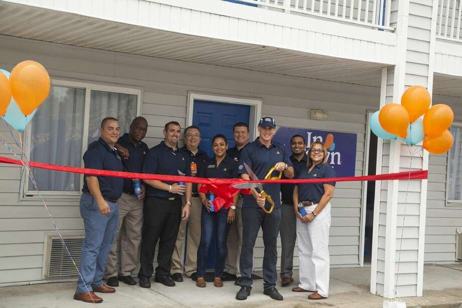 The CEO of InTown Suites, Jonathan Pertchik, surrounded by company team members, cuts the ribbon celebrating the grand reopening of the newly renovated property at 8735 FM 1960 on Thursday, Oct. 22.