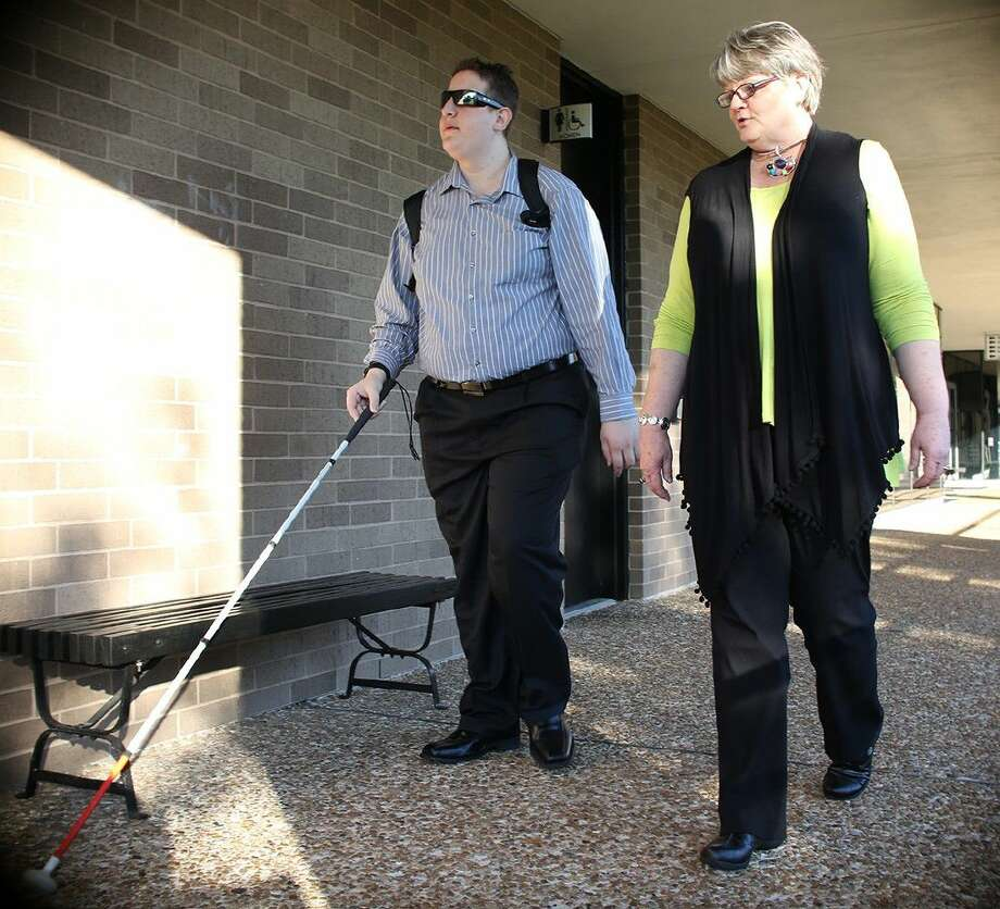 Tamer Zaid, of Friendswood, gets help walking down the sidewalks from Eileen Cross, ACC coordinator for the Office of Disability Services.