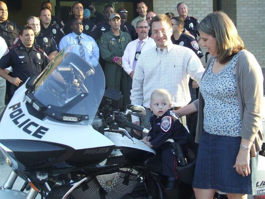 Barry and Kris Heslop help their 20-month-old son, Creighton, while getting on a police motorcycle on Monday, Oct. 19.