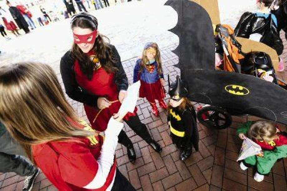 Brandy Williams, Pregancy Assistance Center North finance manager, left, presents an award to Spring resident Sarah Trout and her three daughters for winning first place in the team costume contest during PACN's 4th Superhero Dash on Saturday at Rob Fleming Park in The Woodlands. To view or purchase this photo and others like it, go to HCNPics.com. Photo: Michael Minasi