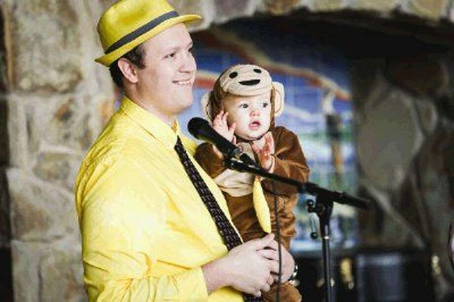 Jordan Bean emcees while holding his 11-month-old daughter Annabelle, dressed as Curious George, during PACN's 4th Superhero Dash on Saturday at Rob Fleming Park in The Woodlands. To view or purchase this photo and others like it, go to HCNPics.com. Photo: Michael Minasi