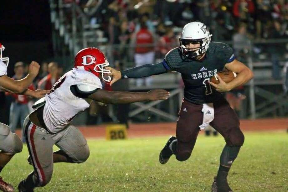 Longhorn quarterback Hunter Johnson (1) stiff-arms a Diboll defender to roll oustide for a touchdown run, Nov. 7, 2014. Photo: Sean Ashley Jones