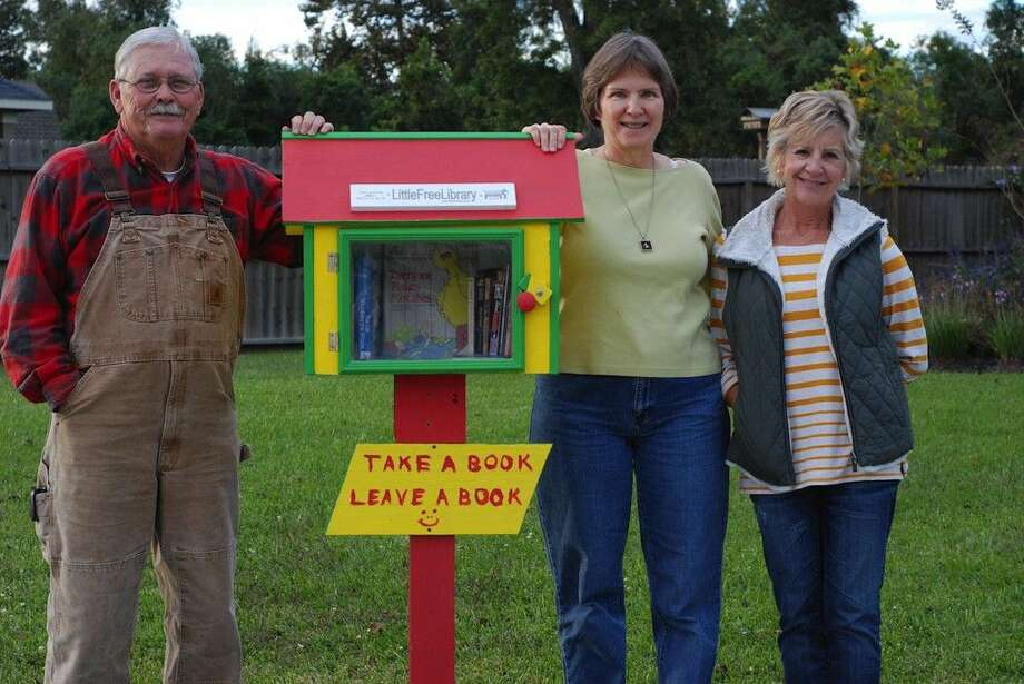 """Lynn and Lori Williams, here with their friend Susan Simmons at right, have put up a """"Little Free Library"""" in front of their home in the Fordland Estates neighborhood of Dayton. Photo: Casey Stinnett"""