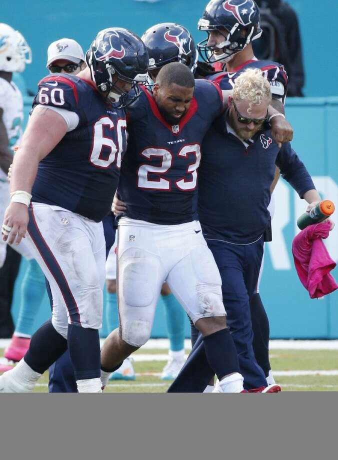 Houston Texans running back Arian Foster, middle, struggles to walk as he is helped off the field by center Ben Jones, left, and an unidentified team member, during the second half of an NFL football game against the Miami Dolphins, Sunday in Miami Gardens, Fla. The Dolphins defeated the Texans 44-26.