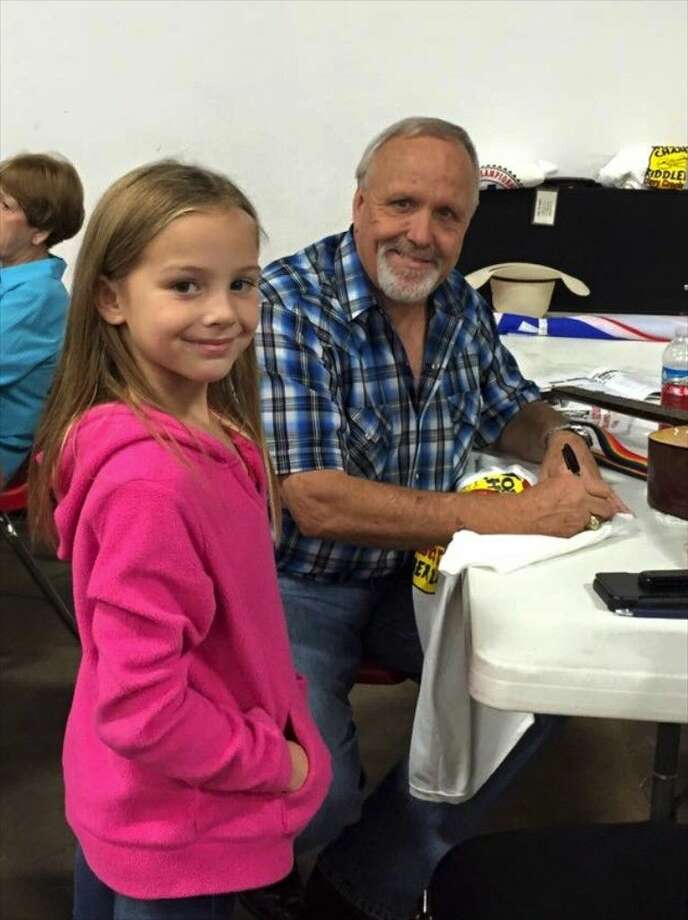 """And every once in a while you get to autograph a T-Shirt,"" Liberty County Judge Jay Knight wrote in his Facebook post of this photo taken by Jan Knight of the county judge with a young fan at the Crockett Civic Center where the county judge placed fourth in the senior division of the 79th annual World Championship Fiddlers' Festival. Photo: Submitted Photo"