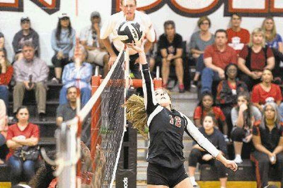 Austin's Mallory Nicholson tips a shot over the net against Dulles, Oct. 20 at Austin High School. The Lady Bulldogs won the match to clinch their third consecutive district championship. To view or purchase this photo and others like it, visit HCNpics.com. Photo: Craig Moseley