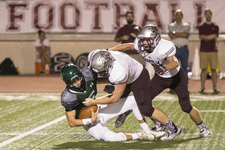 Bulldogs defensive lineman Spencer Nigh (1) sacks Panthers quarterback Zach Purcell (14) during Magnolia's 34-31 victory over Kingwood Park on Aug. 27, 2015, at Turner Stadium in Humble.
