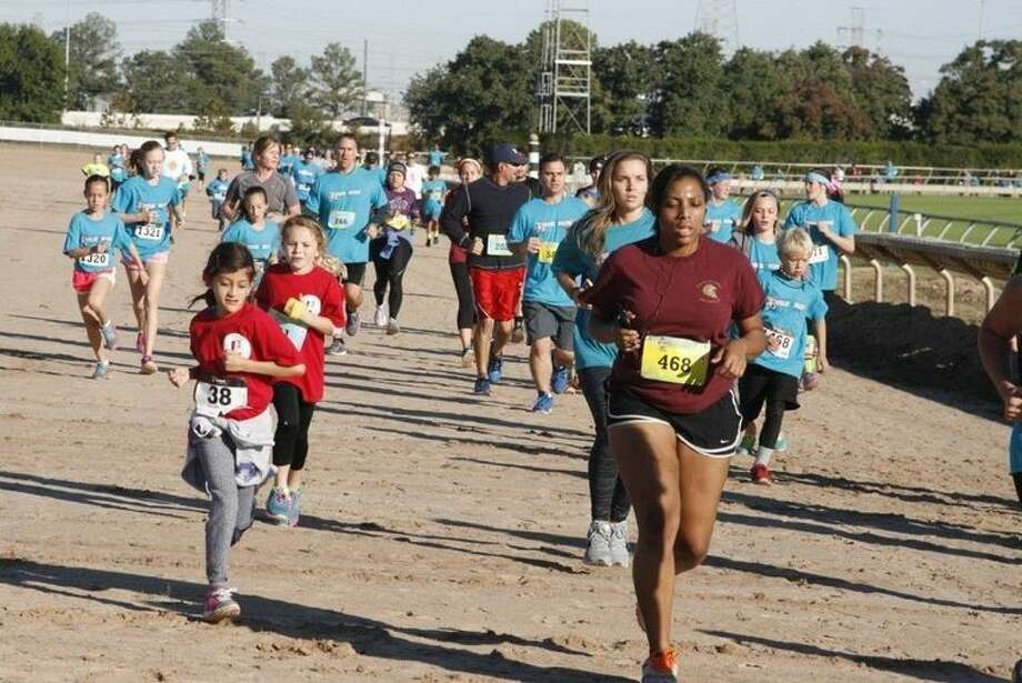Runners make the lap the Sam Houston Race Park for last year's Walk by Faith 5K.