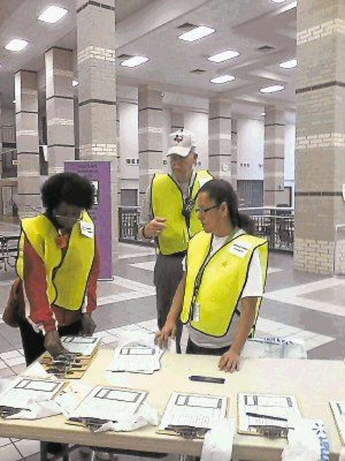 Volunteer greeters prepare clipboards and medical application forms to be completed by heads of households at Station One.