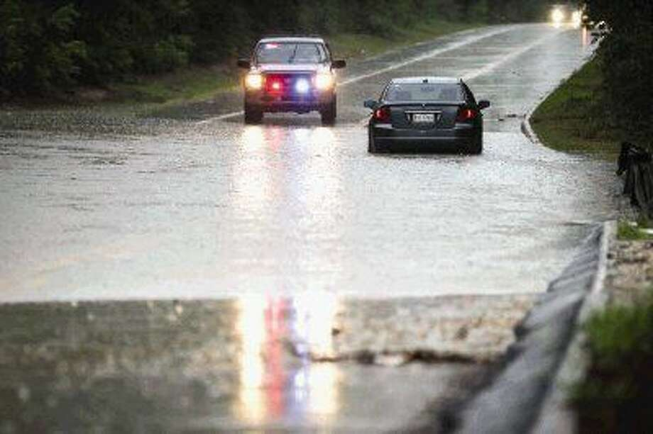 A police officer directs traffic away after a car is stranded in flash flooding on Friday, Sept. 19, 2014, on Research Forest Drive in The Woodlands, Texas. Photo: Michael Minasi