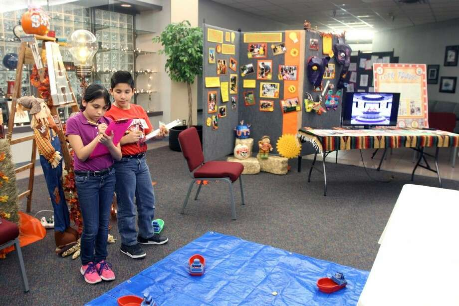 Milstead Middle School fifth grader Denisse Aguilar and sixth grader Yahir Garcia play Battleship during Lights On Afterschool at the Administration Building.