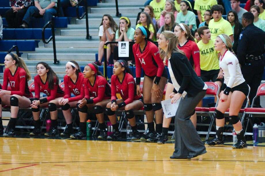 Fort Bend Austin volleyball coach Amy Cataline and the Lady Bulldogs react to play on the court Nov. 10 against Clear Creek at Manvel High School. Photo: Kirk Sides