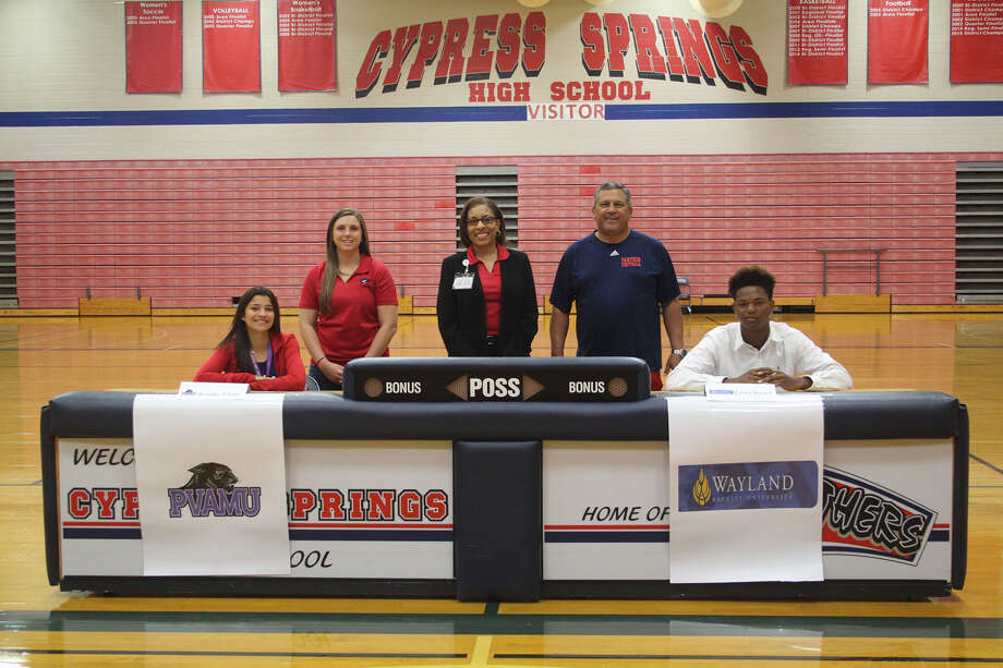 Cypress Springs softball player Brooke Dibler and football player Corey Brown signed with Prairie View A&M and Wayland Baptist, respectively. Pictured with the athletes are (L-R) Tara Murray, assistant softball coach; Dr. Cheryl Henry, principal; and Rick Cobia, head football coach and campus athletic coordinator. Photo: Photo By Antoinette Bahamonde, Cypress Springs HS