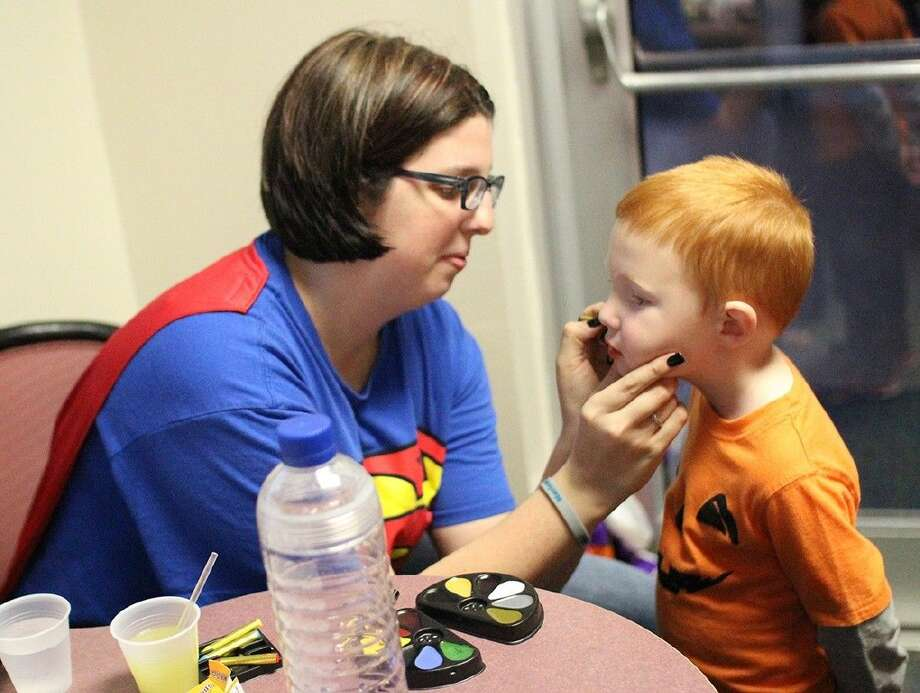 ACC Lab School student Luke Rawls, 4, gets his face painted by teacher Loree Hold during the annual Pumpkin Party on October 30.