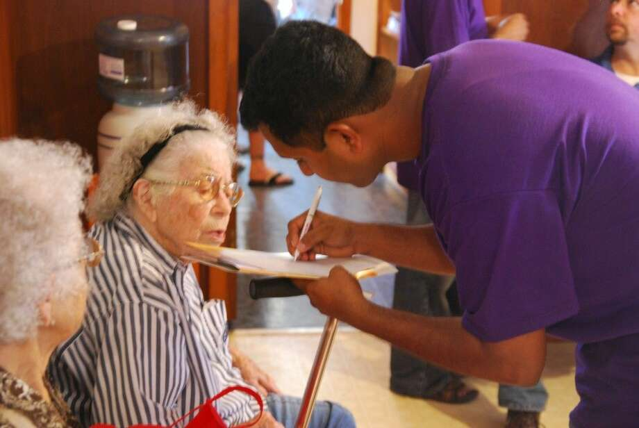 A volunteer helps a 95-year-old participant.