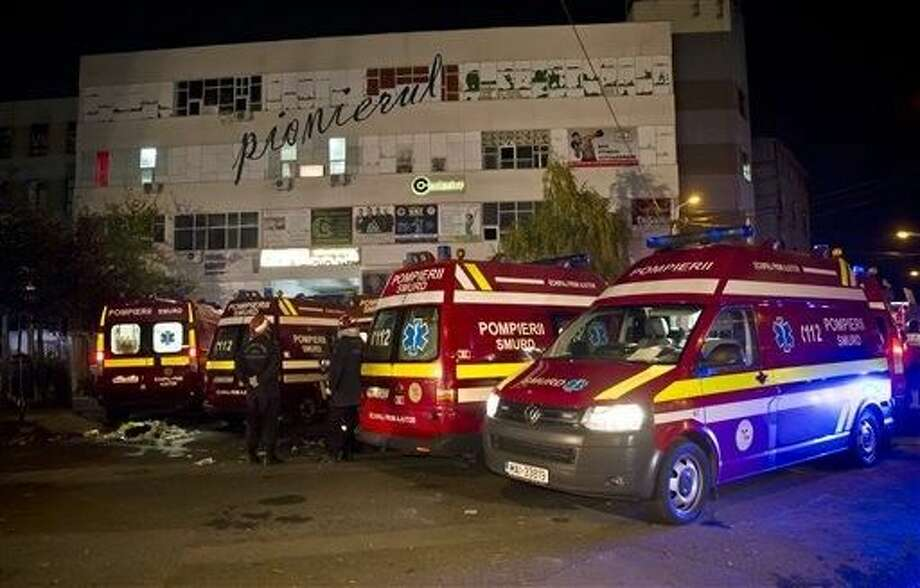 Ambulances are parked outside the site of an explosion that occurred in a club, housed by the building in the background, in Bucharest, early Saturday. An explosion and ensuing flames on a stage at a Bucharest nightclub on Friday left more than 20 people dead and over 150 hospitalized with injuries, Romania's interior minister said. Photo: Vadim Ghirda