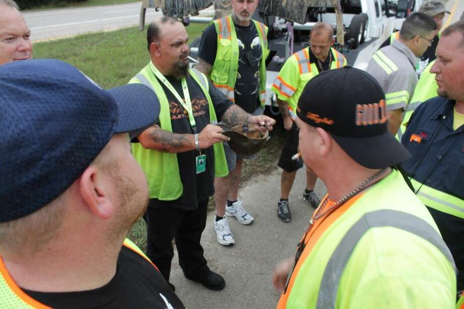 Keith's Towing truck driver Randy Himes accepts chips from tow truck drivers at a car accident on Texas 242 Saturday.