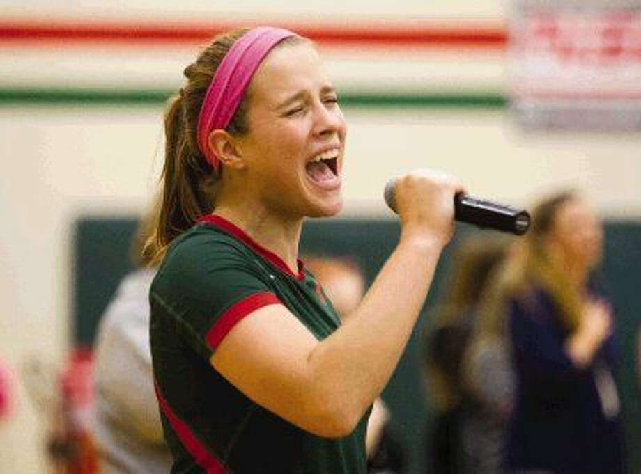The Woodlands Hannah Hickman sings the National Anthem before the varsity volleyball team's game against Kingwood Tuesday. Photo: Jason Fochtman