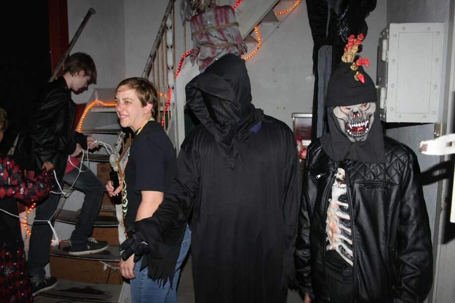 A zombie and a reaper terrorize a new tour group heading upstairs and led by Historical Commission Chair Rebecca Hammond (second from left). Photo: Jacob McAdams