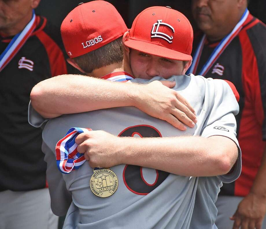 Holding his UIL state semifinal medal, Langham Creek High School senior catcher Mikey Hoehner hugs senior first baseman/pitcher Brady Perez after the Lobos fell to Dallas Jesuit, 2-0, on June 10 at the Dell Diamond in Round Rock.