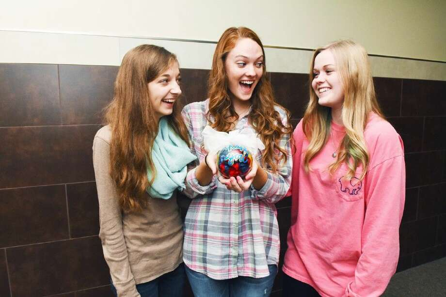 Klein High School are students Emma Gehring, Gracie Mikel and Sarah Horton admire the ornament they created.