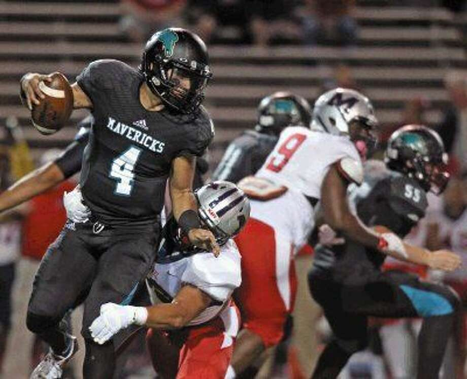Memorial quarterback Izrael Trevino (4) tries to get away from a Manvel player Thursday night. Photo: Kar B Hlava