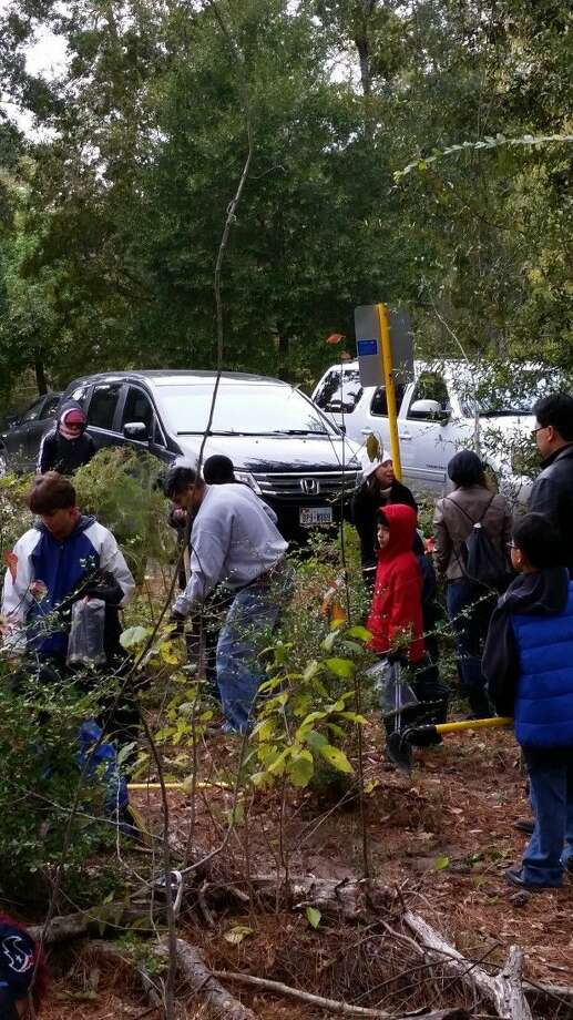 Cub Scouts log community service hours by planting young trees in Jesse Jones Park in Humble.