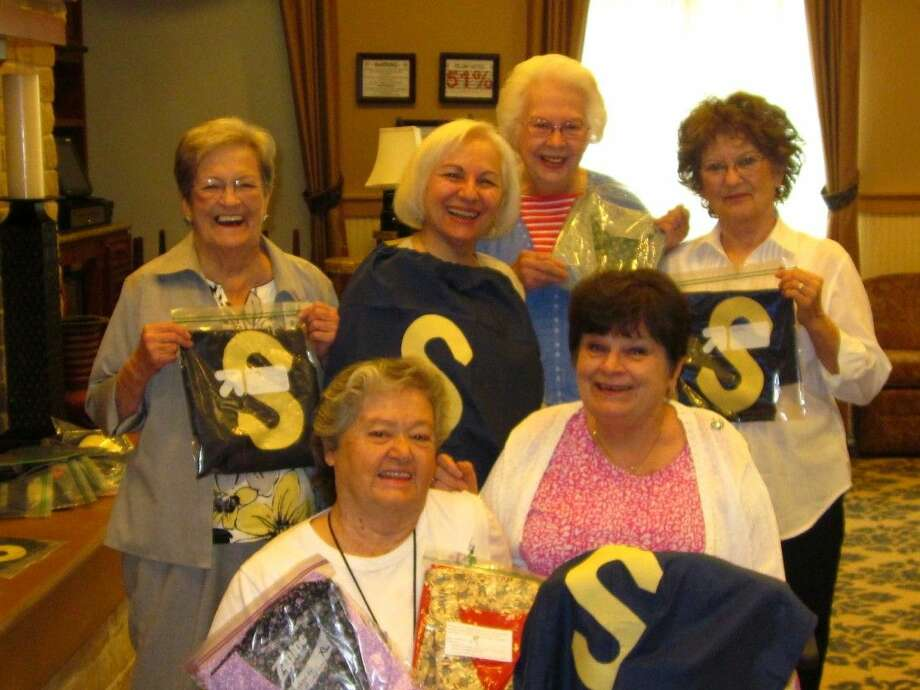 Residents of Eagle's Trace retirement community created hero capes and modesty smocks for patients at Houston-area hospitals in October. Pictured in the front row (left to right) are Mary Wright and Pat Coatsworth. Ann Foster, Louise Baldaro, Margo Goertz, and Karen Brooks are photographed in the back row, left to right.