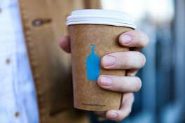 Miles Morris holds a cup of coffee on his way out of Blue Bottle Coffee in Oakland, California, on Tuesday, Oct. 4, 2016.