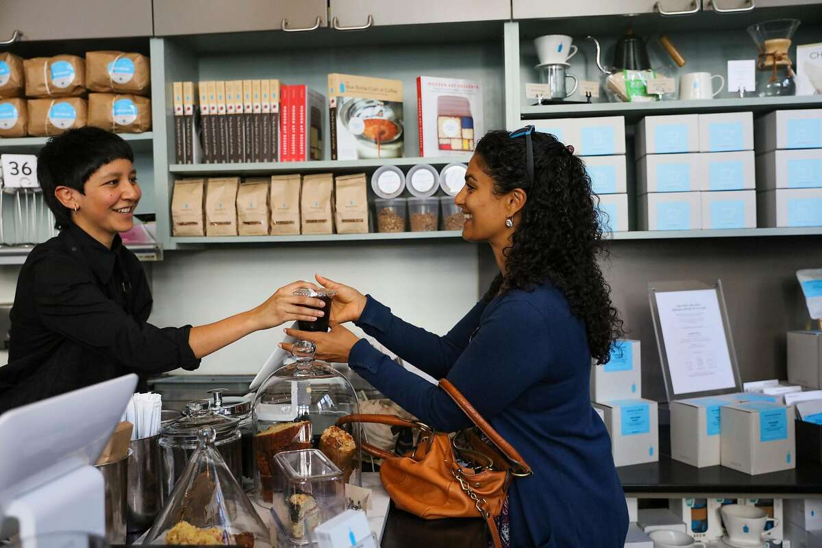 Christine Attia (right) grabs her coffee from barista Gabby Gamboa (left), inside Blue Bottle Coffee at Mint Plaza, in San Francisco, California, on Tuesday, Oct. 4, 2016.