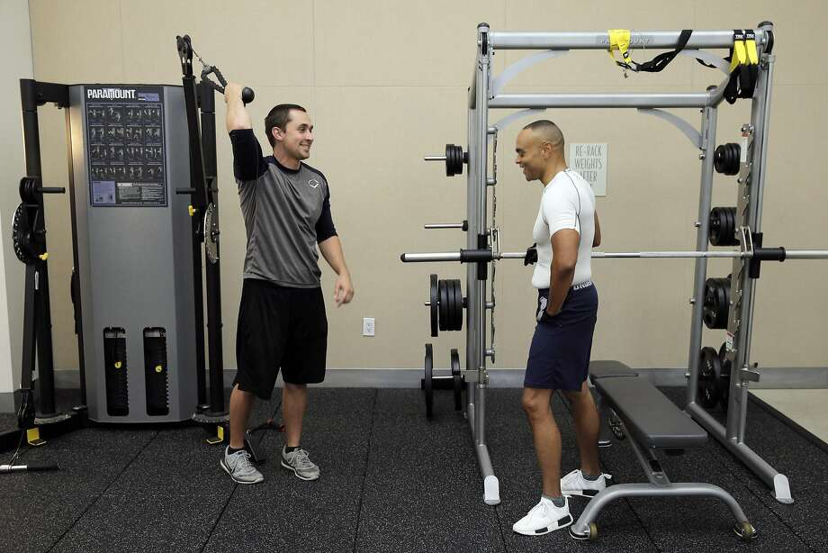 Baron Lambert (left) works with his client, Chris Barbour, at Barbour's condominium gym in San Francisco. Lambert left his regular job as a fitness trainer at 24-Hour Fitness to go into business for himself, like many Americans in recent years. Photo: Carlos Avila Gonzalez, The Chronicle