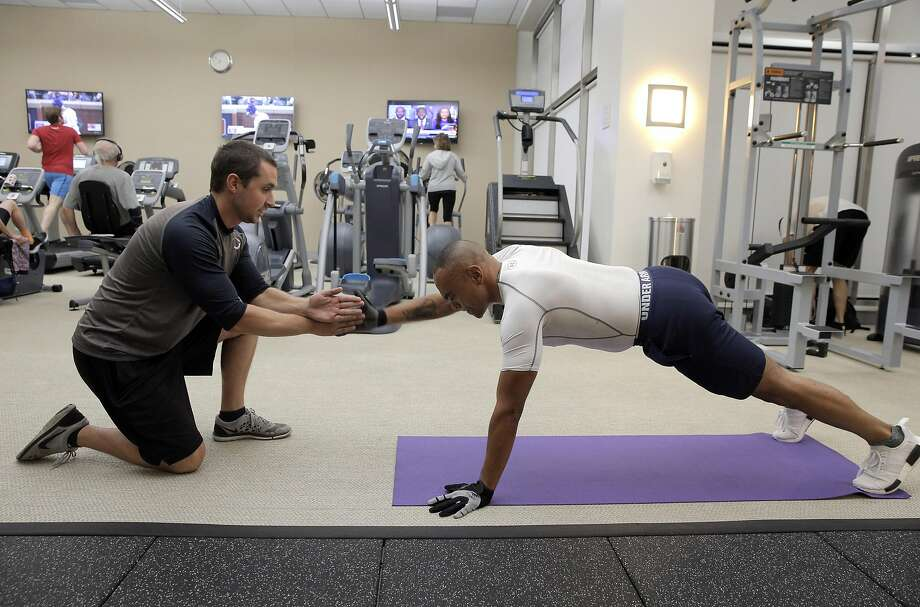 Baron Lambert, left, works with his client, Chris Barbour, at Barbour's condominium gym in San Francisco, Calif., on Wednesday, October 5, 2016.  Lambert left his regular job as a fitness trainer at 24-Hour Fitness to go into business for himself, similar to many americans in recent years. Photo: Carlos Avila Gonzalez, The Chronicle